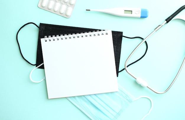 Blocco note che si trova su uno sfondo blu accanto a un termometro e maschere mediche. concetto medico
