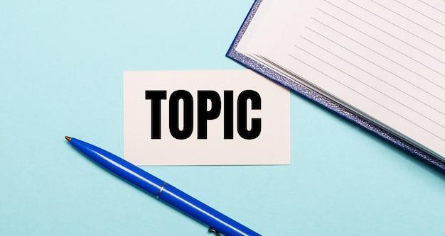 Blocco note, penna bianca e carta con la scritta topic su sfondo blu. vista dall'alto