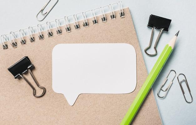 Blocco note, adesivo bianco e penna sulla scrivania