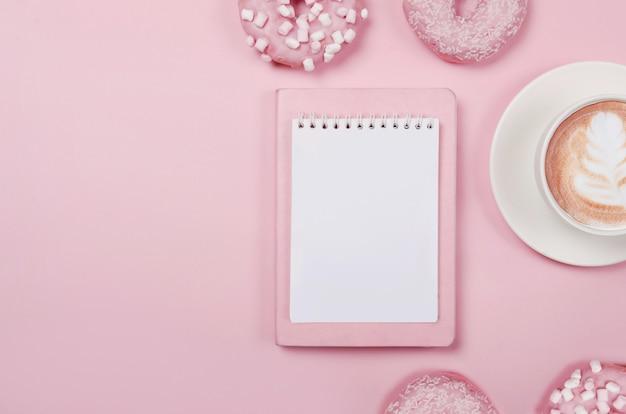 Lista dei desideri del blocco note per progetti futuri. composizione piatta laica con ciambelle, blocco note e tazza di caffè