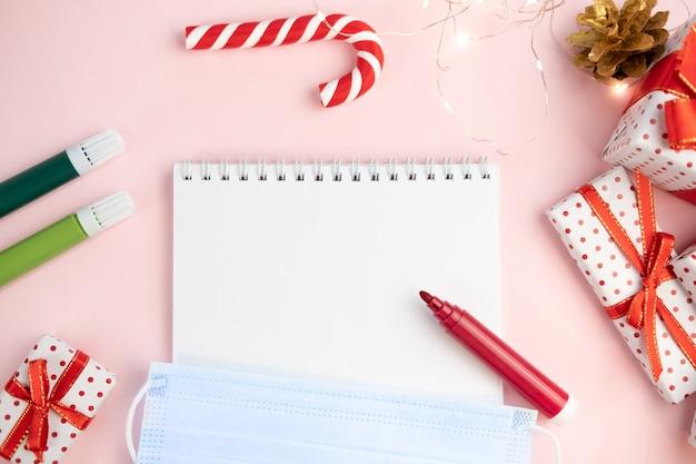 Lista dei desideri del blocco note su un tavolo rosa con pennarelli con maschera protettiva su uno sfondo di natale. concetto di natale, capodanno, piani e desideri e corona virus