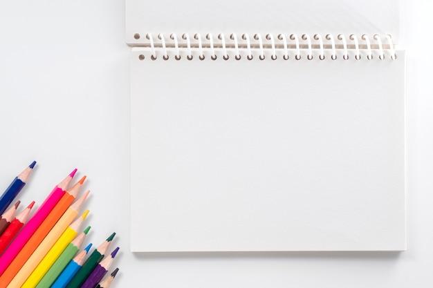 Blocco note con matita colorata su tavolo bianco vista dall'alto