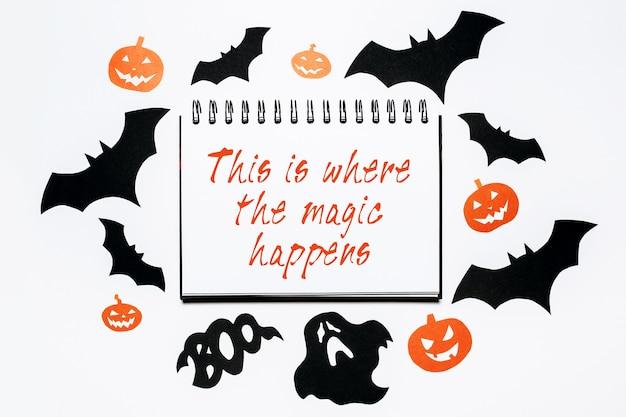 Blocco note con testo di halloween qui è dove avviene la magia su sfondo bianco