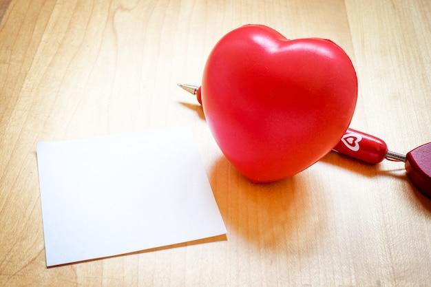 Blocco note con il giocattolo del cuore e penna rossa sulla tavola di legno, concetto di amore