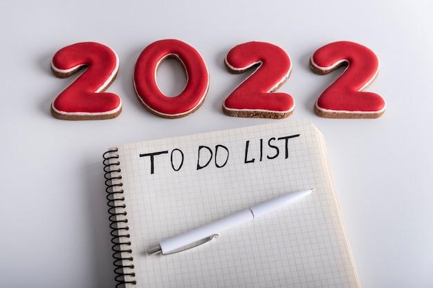 Blocco note con scritta to do list penna e numeri 2022 su sfondo bianco. avvicinamento. piani e obiettivi per il 2022