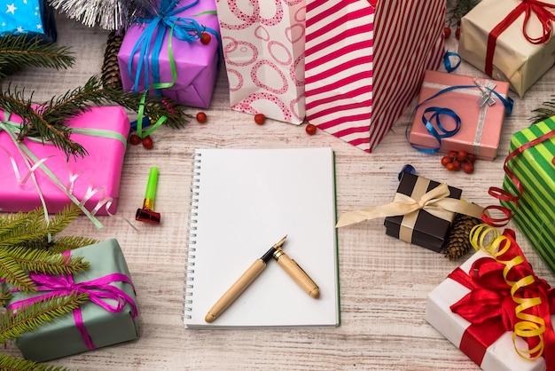 Blocco note con penna e scatole regalo colorate sul tavolo di legno. celebrazione e regali