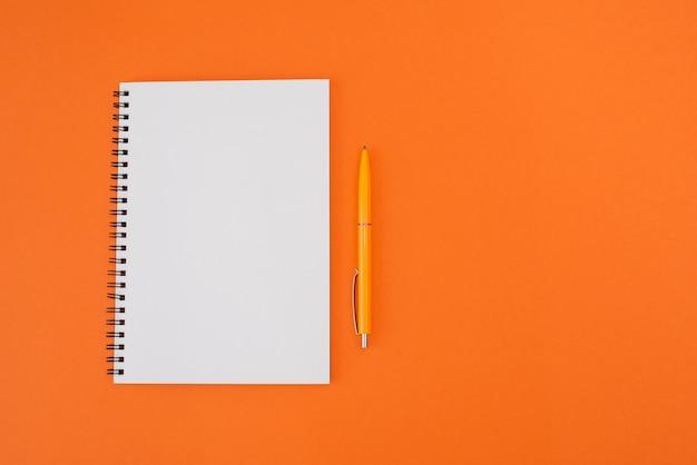 Blocco note con una penna su uno sfondo arancione con spazio di copia. disposizione piatta.