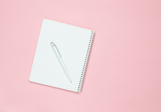 Blocco note con penna su uno sfondo rosa pastello, vista dall'alto, tendenza minimalismo