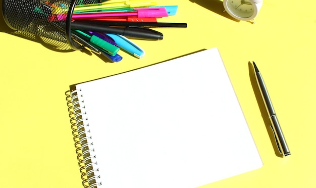 Blocco note con posto per il testo. cartoleria nelle vicinanze. colore di sfondo giallo.