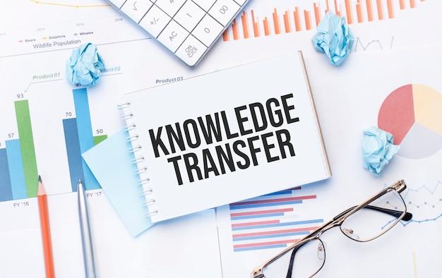 Blocco note con tex trasferimento della conoscenza sui grafici aziendali e penna, affari