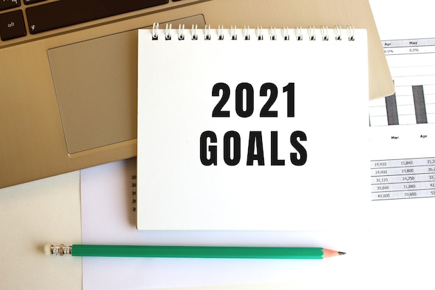 Il blocco note con il testo obiettivi 2021 è sulla tastiera del laptop. spazio di lavoro minimo.