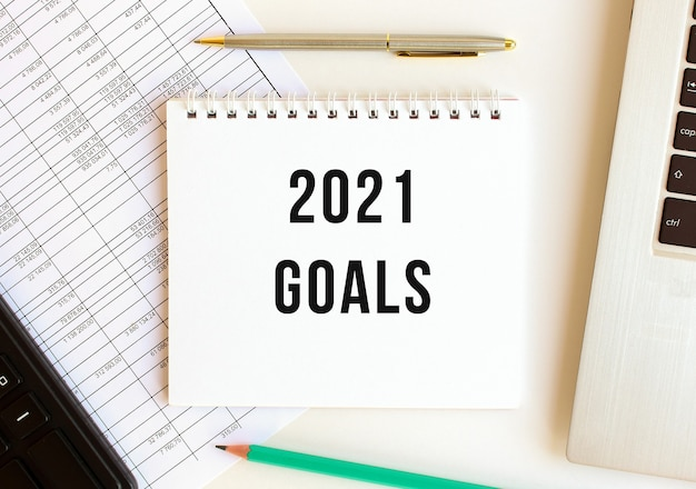 Blocco note con testo 2021 obiettivi su una superficie bianca, vicino a laptop e calcolatrice