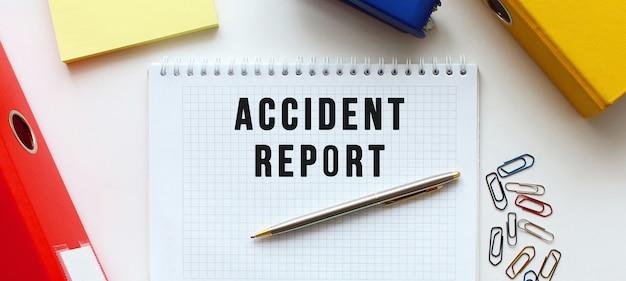Blocco note con testo rapporto di incidente su uno sfondo bianco, vicino alla cartella documenti e forniture per ufficio