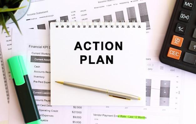 Blocco note con testo piano d'azione su un taccuino bianco, vicino a calcolatrice e forniture per ufficio. concetto di affari.