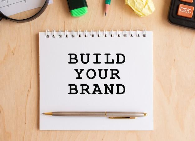 Blocco note con testo costruisci il tuo marchio su un tavolo di legno, vicino a calcolatrice e forniture per ufficio. concetto di affari.