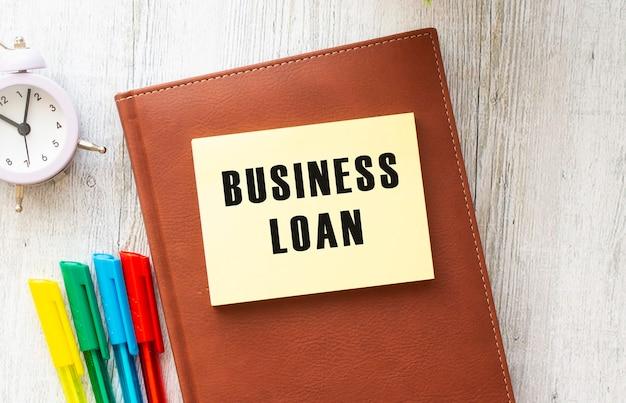 Blocco note con testo prestito affari su uno sfondo bianco, vicino a laptop, calcolatrice e forniture per ufficio