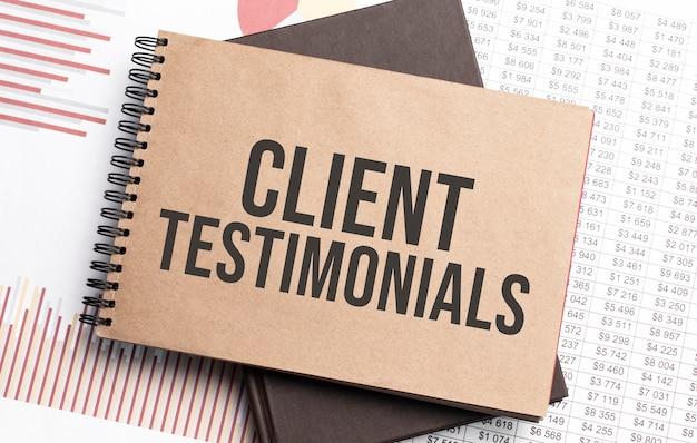 Blocco note con testo testimonianze dei clienti su grafici e numeri. concetto di affari.