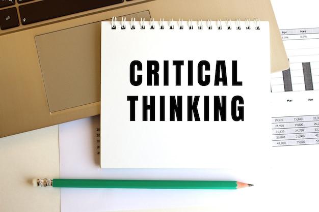 Il blocco note con il testo critical thinking è sulla tastiera del laptop.