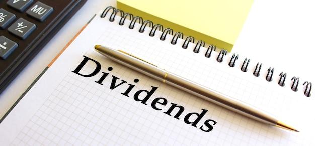 Blocco note con testo dividendi su uno sfondo bianco, vicino alla calcolatrice e fogli di nota gialli.