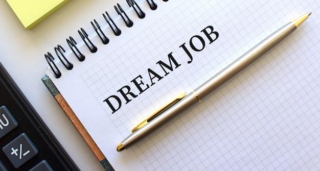 Blocco note con testo lavoro da sogno, accanto ad esso si trova una calcolatrice. concetto di affari.