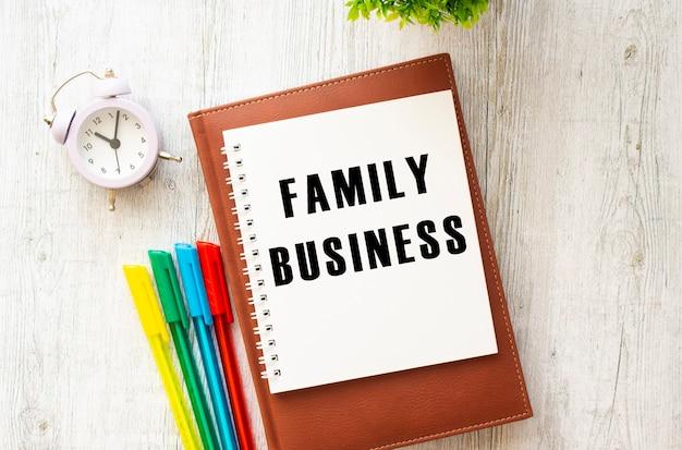 Blocco note con il testo family business su un tavolo di legno. diario e penne marroni. concetto di affari.