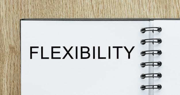 Blocco note con flessibilità del testo sulla scrivania in legno. concetto di affari e finanza