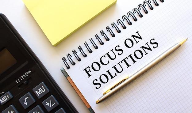 Blocco note con testo focus on solutions, accanto si trova una calcolatrice e fogli di nota gialli