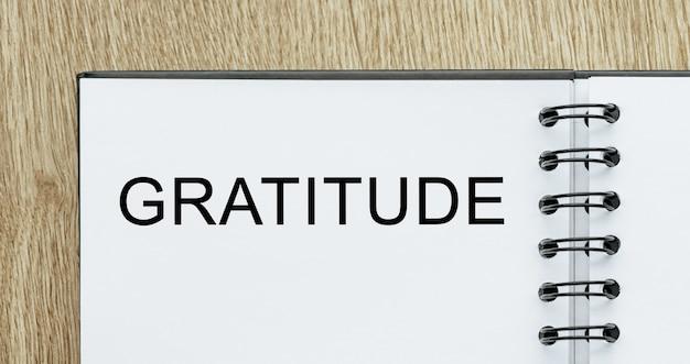 Blocco note con testo gratitudine sulla scrivania in legno. concetto di affari e finanza