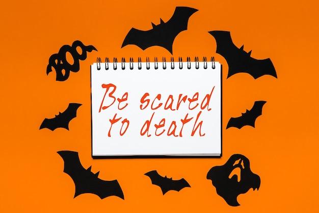 Blocco note con testo halloween spaventati a morte su sfondo bianco e arancione