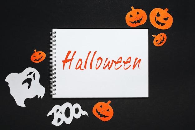 Blocco note con testo halloween su sfondo nero con pipistrelli, zucche e fantasmi Foto Premium