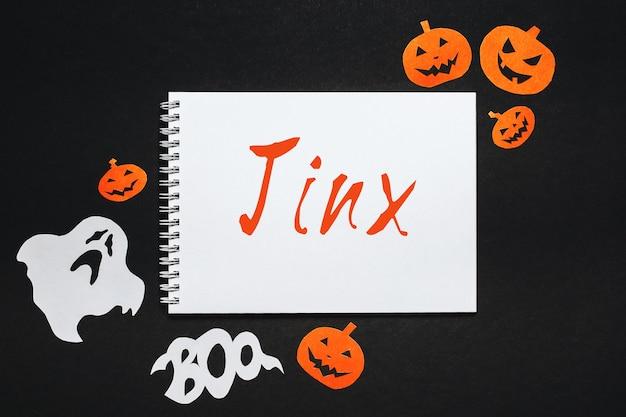 Blocco note con testo halloween jinx sulla superficie nera