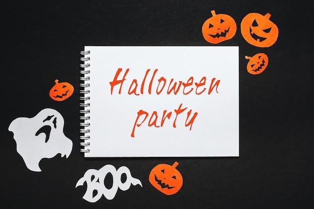 Blocco note con testo festa di halloween su sfondo nero con pipistrelli, zucche e fantasmi