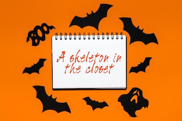 Blocco note con testo halloween uno scheletro nell'armadio su uno spazio nero
