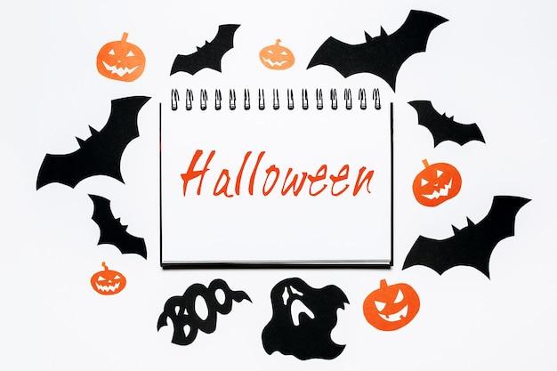 Blocco note con testo halloween su sfondo bianco con pipistrelli, zucche e fantasmi