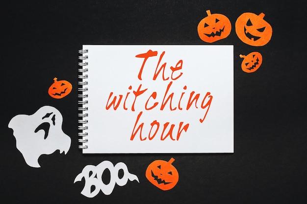 Blocco note con testo halloween l'ora delle streghe sullo spazio nero con pipistrelli, zucche e fantasmi