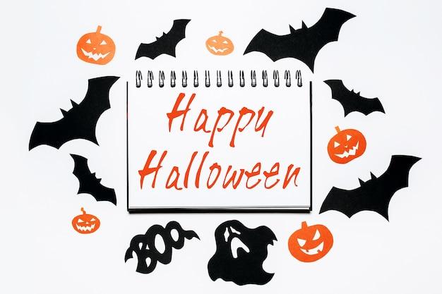 Blocco note con testo happy halloween su sfondo bianco con pipistrelli, zucche e fantasmi