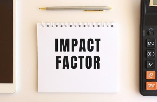 Blocco note con testo fattore di impatto su uno sfondo bianco, vicino a calcolatrice, tablet e penna.