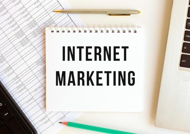 Blocco note con testo marketing internet su uno sfondo bianco, vicino a laptop, calcolatrice e forniture per ufficio. concetto di affari.