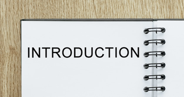 Blocco note con testo introduzione sulla scrivania in legno. concetto di affari e finanza