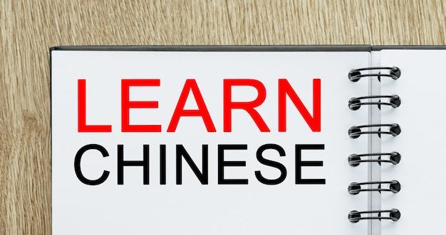 Blocco note con testo impara il cinese sulla scrivania in legno. concetto di studio e istruzione