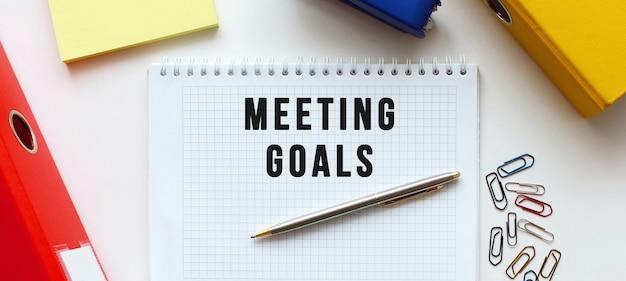 Blocco note con testo riunione obiettivi vicino alla cartella dei documenti e alle forniture per ufficio