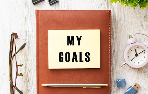 Blocco note con il testo i miei obiettivi su un tavolo di legno. diario e penna marrone. concetto di affari.