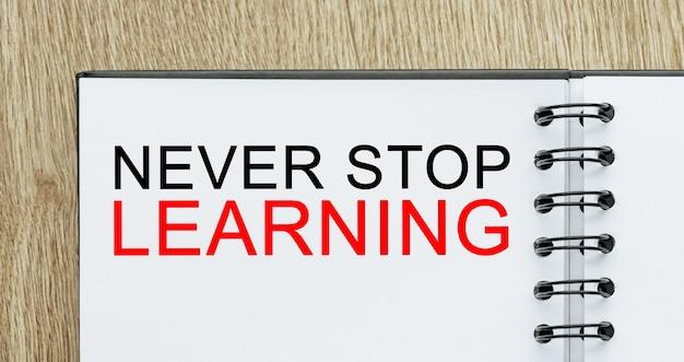 Blocco note con testo non smettere mai di imparare sulla scrivania in legno. concetto di affari e finanza