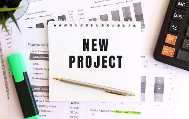 Blocco note con testo nuovo progetto su uno sfondo bianco, vicino a pennarello, calcolatrice e forniture per ufficio. concetto di affari.