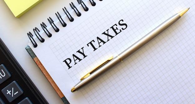 Blocco note con testo pagare le tasse, accanto si trova una calcolatrice e fogli di nota gialli.