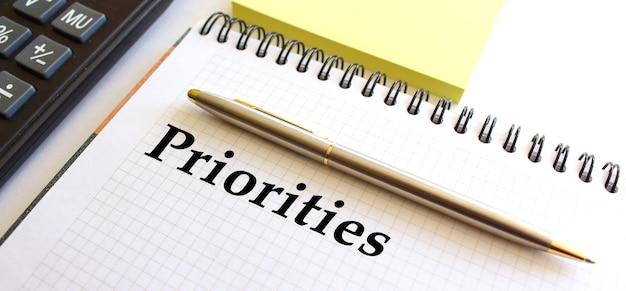 Blocco note con le priorità del testo su un tavolo bianco, vicino alla calcolatrice e ai documenti per appunti gialli. concetto di affari.