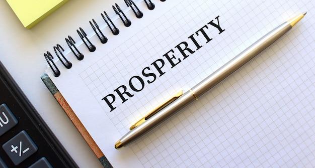 Blocco note con testo prosperità, accanto ad essa si trova una calcolatrice e fogli di nota gialli.