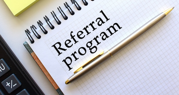 Blocco note con testo referral program. concetto di affari.