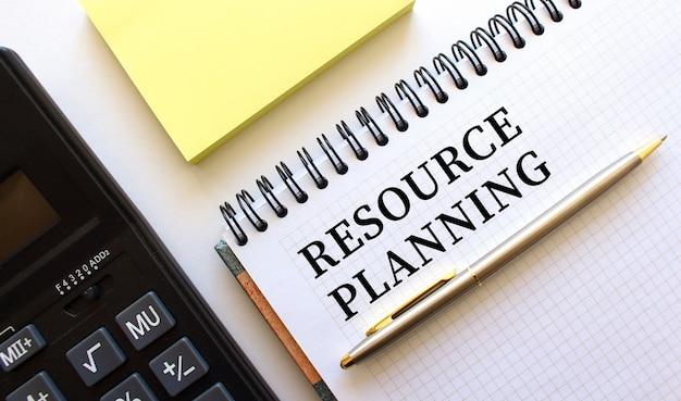 Blocco note con testo pianificazione delle risorse, accanto si trova una calcolatrice. concetto di affari.