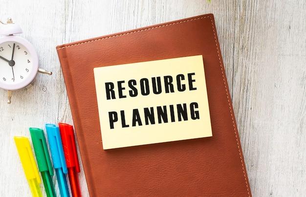 Blocco note con testo pianificazione delle risorse su uno sfondo bianco, vicino a laptop, calcolatrice e forniture per ufficio